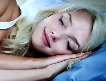 Young woman sleeping peacefully at night in bed